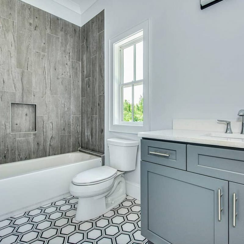 Wood look tile tub surround and a hexagon porcelain tile floor