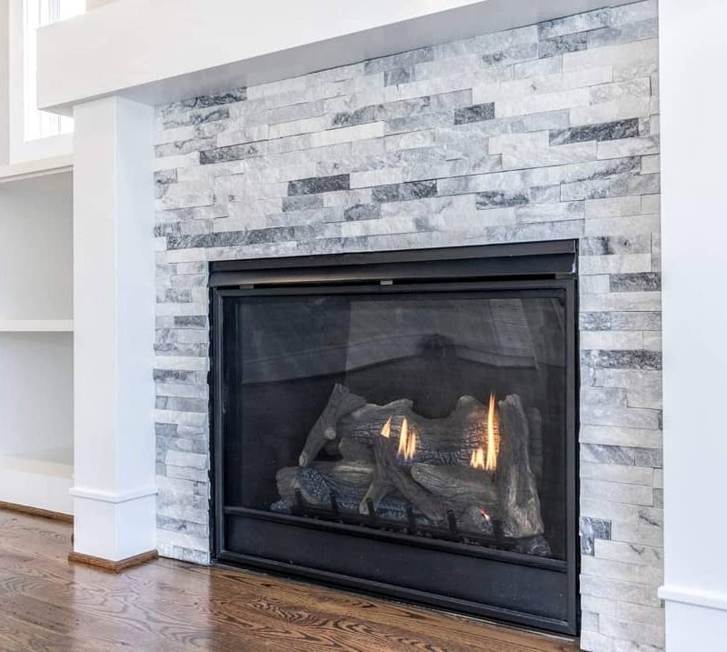 White and grey splitface quartzite stacked stone fireplace