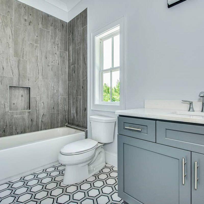Wood look tile tub surround and a hexagon porcelain tile floor